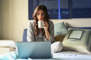 woman on bed on a computer, working remotely